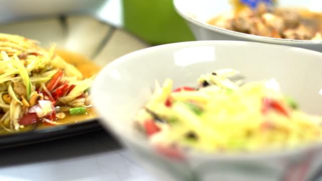 Thai papaya salad on wooden table video