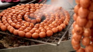 Thai style grilled round sausages on a stove. video