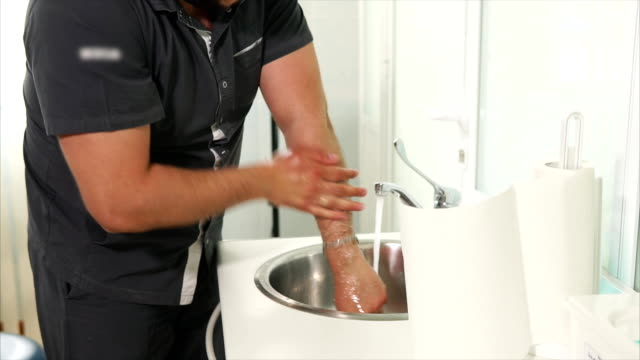The adult doctor carefully washes his hands before putting on latex gloves video