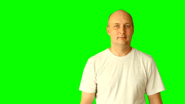 The adult man smiles and nods his shaking head. He gestures with his hands and head. Studio shooting model on a green background. Prepared as a template for advertising. video