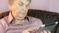 The aged woman holding the silver tablet computer video
