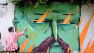 The artist draws graffiti on a fence. video