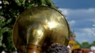 The back of a big tuba in a band video
