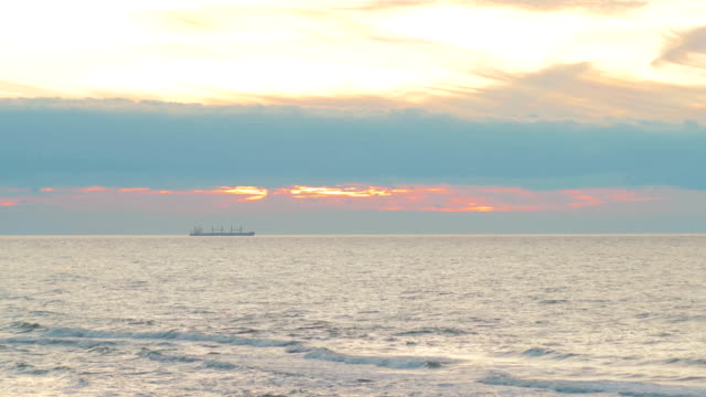 The balker stands at anchor amid a beautiful sunset sky. Stormy sea, waves, wind, colorful clouds video