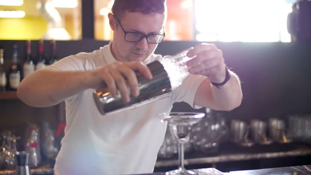 The bartender at the restaurant prepares a cocktail . Slow motion video