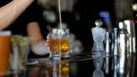 The bartender stirs years and alcohol in a glass video