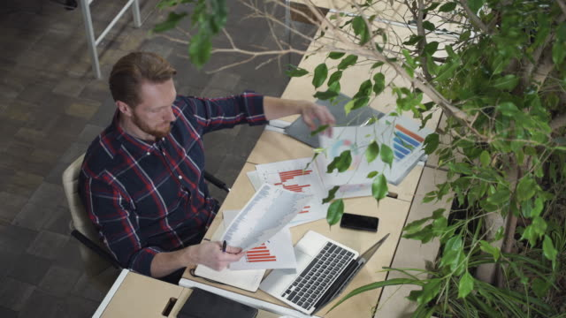 The bearded man sits in the environmental office and looks at the figures on paper video