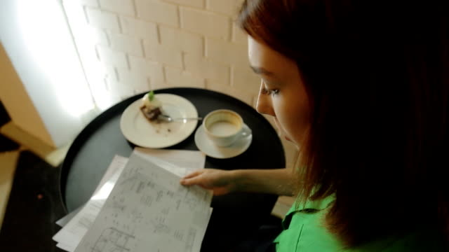 The beautiful woman is sitting in cafe working with the blueprints, drawings, plans of houses and buildings video