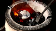 The blacksmith straightens the crucible in the furnace with a poker video