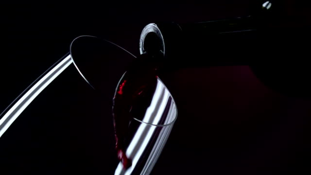 The bottle of wine, the wine is poured into a glass, black, closeup, slowmotion video