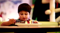 The boy is eating a piece of cake with a spoon video