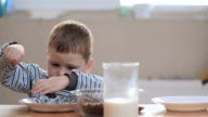 The boy puts the flakes in his plate video