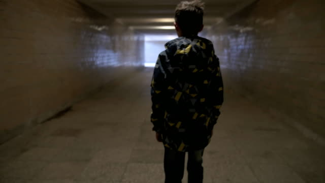 The boy walks through the tunnel, goes to the exit from the tunnel video