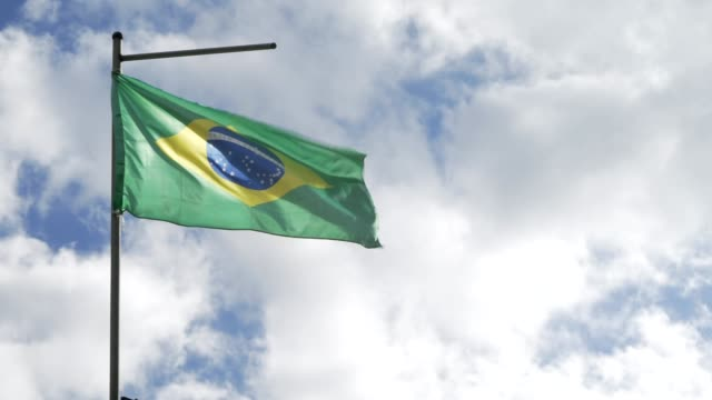 The Brazilian flag flutters in the wind against the background of clouds video