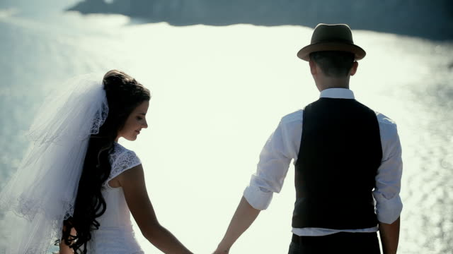 the bride and groom on a cliff above the ocean, holding hands video