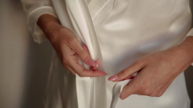 The bride , dressing gown is sitting on the bed. Wedding video