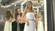 The bride fitting white wedding dress in salon video