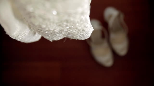The bride wears white wedding shoes with her hands video
