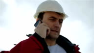 The builder in a white helmet with a mobile phone. video