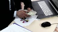 The businessman is working at the desk, examining reports and counting money. video