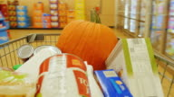 The buyer carries a cart with purchases through the store. The trolley is also a pumpkin. Preparing for Halloween video