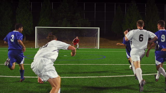 The camera follows a soccer player down the field as he makes a goal video