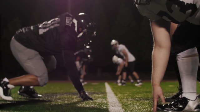 The camera pulls back through football players at the line of scrimmage as the ball is snapped video