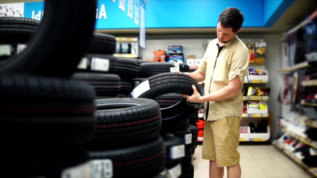 The car enthusiast choosing tires in the mall for his car. Man looking carefully video