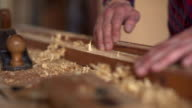 The carpenter sweeps the shavings off the wood with wood video