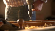 The carpenter uses a hand-held vintage drill in his work place. Slow motion video