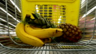 The cart in a supermarket. Bananas and pineapple are put in the cart. video