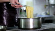 The chef cooks spaghetti on the pro-kitchen video