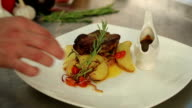 The chef finishes the dish. The decoration of dishes. Juicy steak with fried potatoes. Roast the vegetables. Gravy boat. The meat on the grill. Cherry tomatoes. The restaurant's cuisine. video