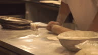 The chef prepares the pizza.Thin dough.Rolls out the dough. The kitchen in the restaurant. video