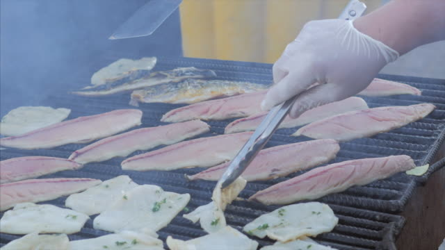 The chef toils over an open grill frying fish, rapans and squid. Cooking mackerel fillet at grill for fish durum video