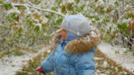 the child looks at the snow falling in the park video