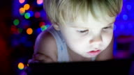 The child looks to the tablet lying on bed. In the background, lights and garlands of Christmas fir video