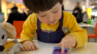 The child playing with smartphone in the cafe video