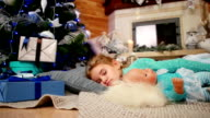 The child sleeps near a Christmas tree, little cute girl hugging a doll during sleep, sweet sleep in the living room near the fireplace where the fire burns video
