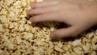 The child takes the popcorn, close-up video