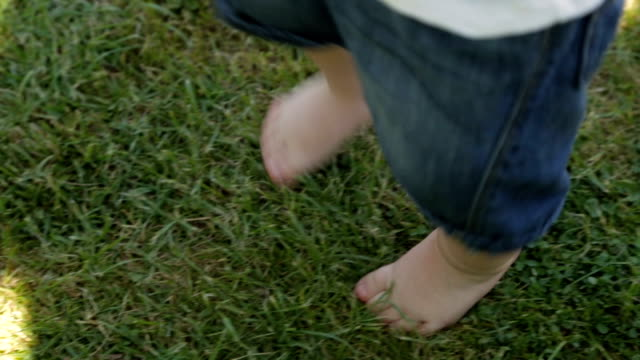 The child walks barefoot on the green grass video