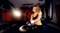 The close-up of the girl boxer putting on boxer gloves. 4K video