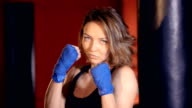 The close-up portrait of the girl boxer posing. 4K video