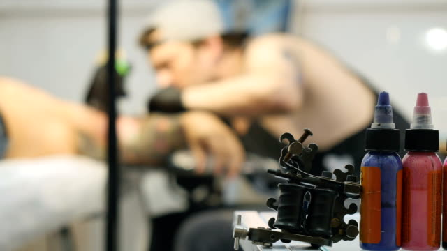 The colorful paints in focus, the tattooist is working on blurred background video