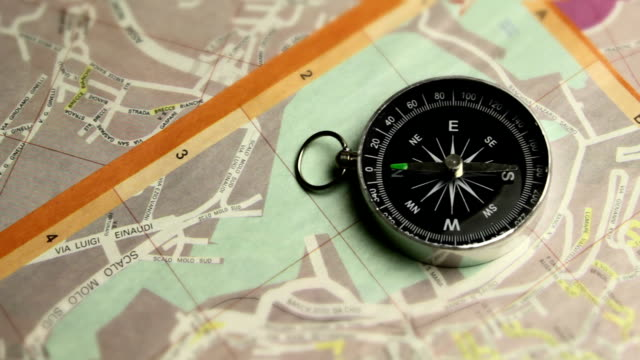 The compass indicates the right path on map of city in italy video