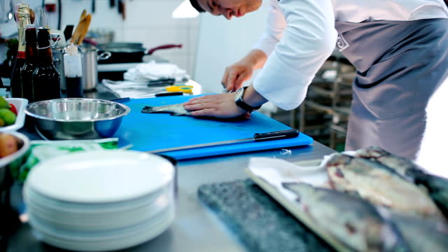 The cook cutting the raw fish into two pieces at the board video