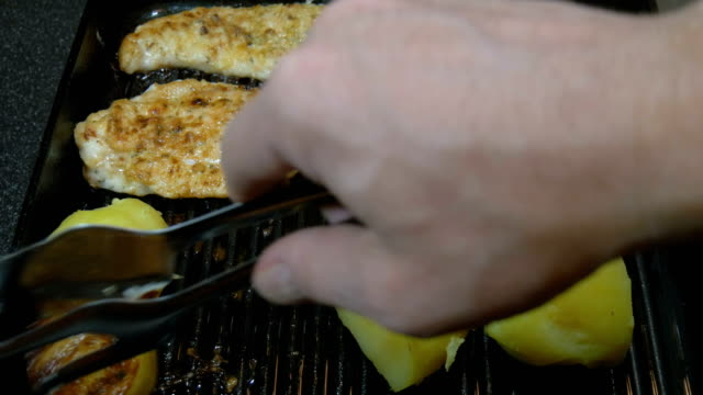 The cook fries potatoes and turkey fillets on the grill. video
