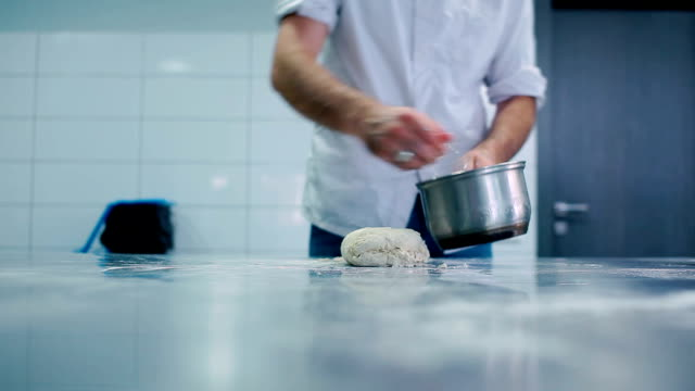 The cook is knead the dough at the table video