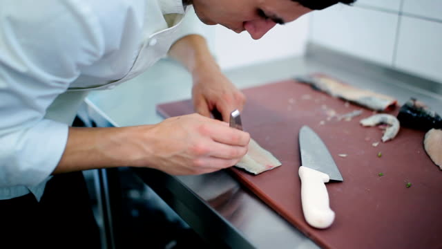 The cook unbones the fish fillet at the board video