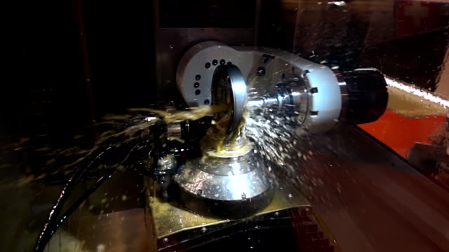 The cooling liquid is poured on the detail on the milling machine. Slow mo video